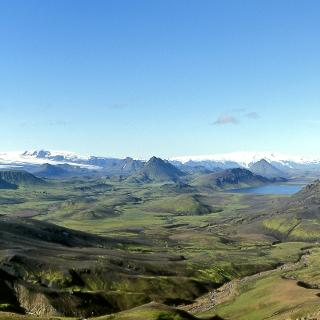 View to the south over moss-covered volcanic cones up to the glaciers Eyjafjallajökull and Mýrdalsjökull