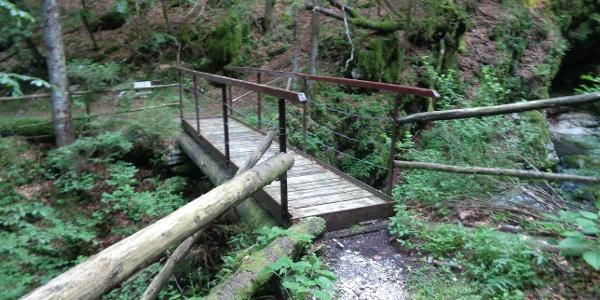 Vom Parkplatz steigen Sie zum Wildbachbett hinab und über die Brücke