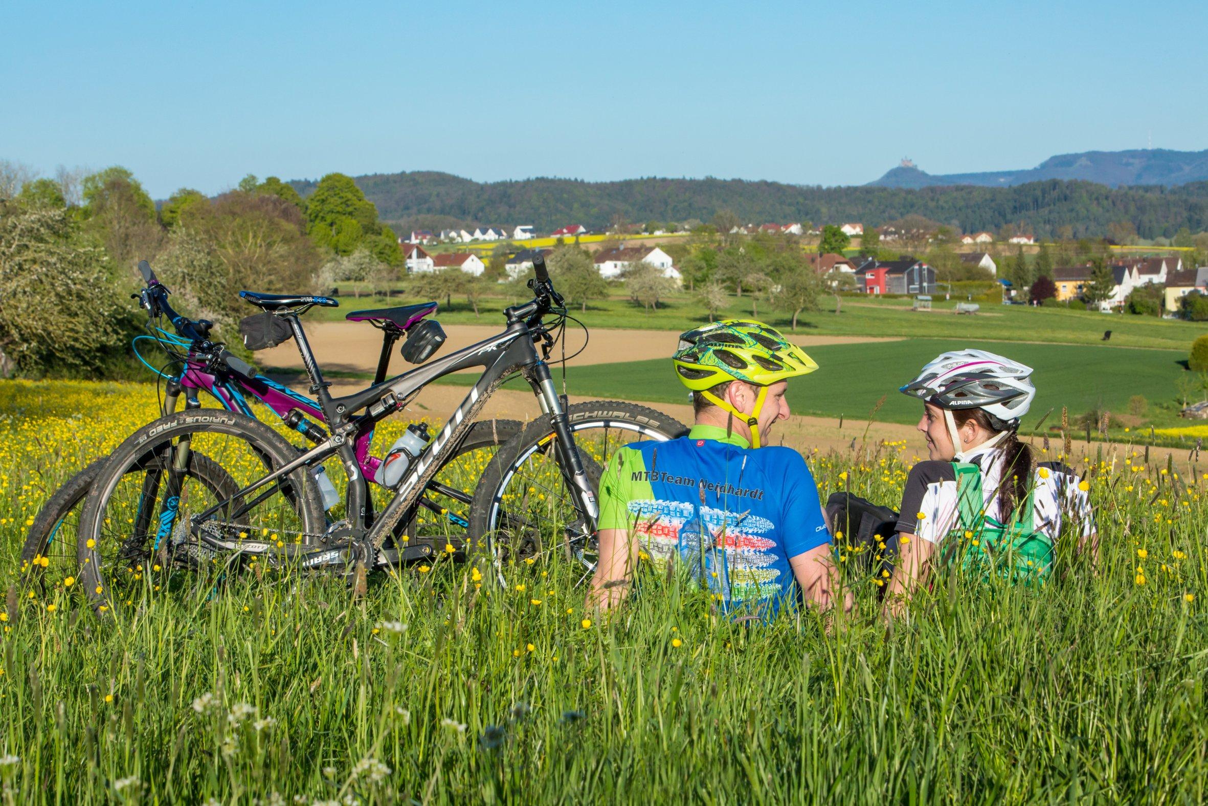 Zwei Radfahrer sitzen in der Wiese bei der Rast und schauen sich an. Nebenan die Fahrräder und im Hintergrund das Albpanorama mit Burg Hohenzollern