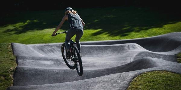 Frau mit Bike springt im Pumptrack