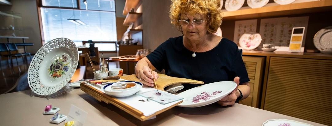 Künstlerin in Schauwerkstatt der Porzellanmanufaktur