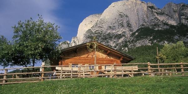 Die Hütte der Tuffalm unter den Felswänden des Schlerns