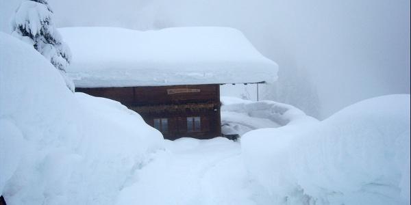 Die tief verschneite Mariolbergalm lädt in die warme Stube.