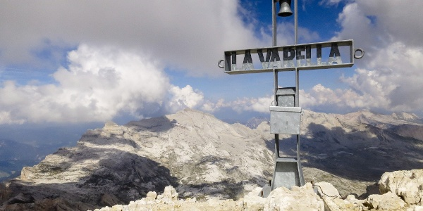 The summit cross with the bell on the Piz Lavarela mountain in the natural parc Fanes.