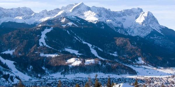 Hinter der Eckenhütte erhebt sich das Wettersteingebirge mit Alpspitze und Zugspitze.