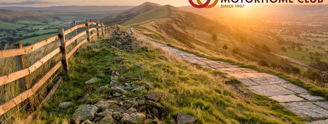 Stone footpath and wooden fence leading a long The Great Ridge in the English Peak District.