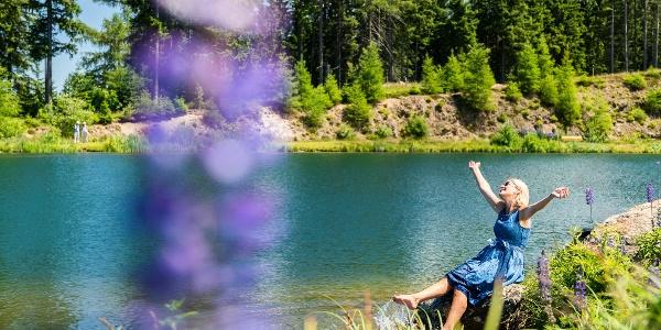 Junge blonde Frau am Ufer des Hebalmsees