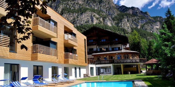 The Piné hotel lies idyllic under the cliffs of the Dolomites in Tires.