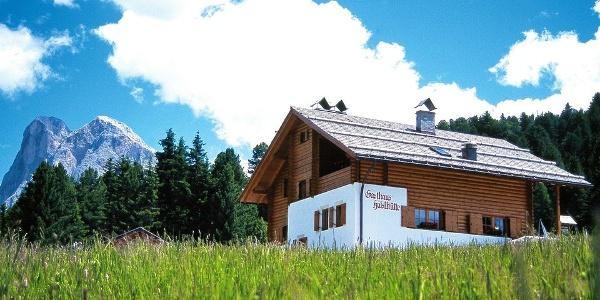 Wie aus dem Bilderbuch: die Halslhütte bei Villnöss auf saftig grünen Almwiesen.