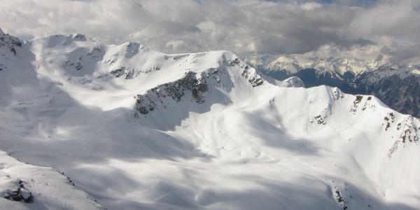 Über die sonnenbeschienen Hänge unmittelbar hinter dem markanten Felsgrat erreicht man den Gipfel (Aufnahme vom Gipfel des Schafzolls).