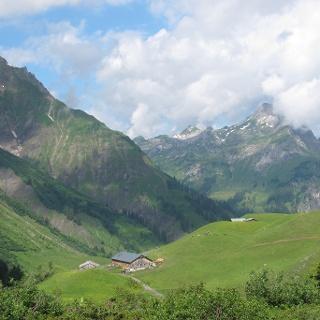 Die Batzenalpe, in deren altem Gebäude sich das Alpmuseum uf m Tannberg befindet. Dahinter ist die Walser Heimat uf m Büel zu erkennen. Im Hintergrund die Hochkünzelspitze