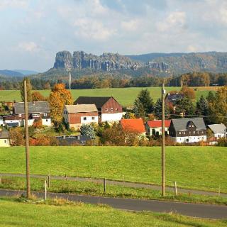 Kleinhennersdorf mit den Schrammsteinen im Hintergrund